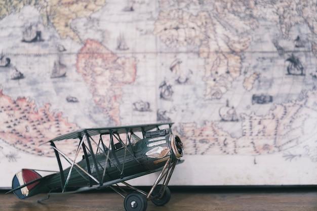 Toy biplane against world map Free Photo
