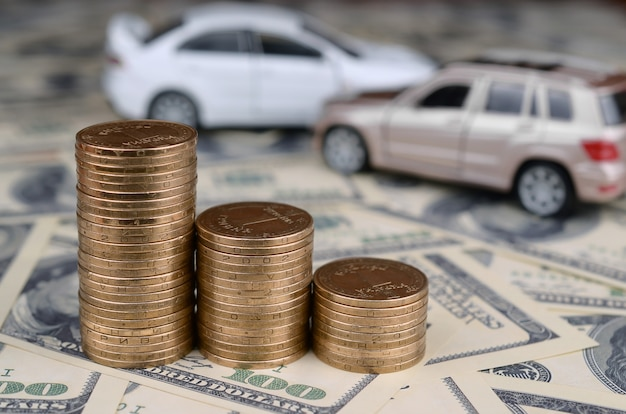 Toy car in accident on a  of 100 dollar bills and stacks of golden coins Premium Photo