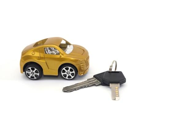 おもちゃの車と白い背景で隔離の鍵。自動購入の概念。 Premium写真