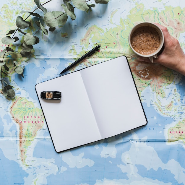 Toy car on blank diary and hand holding coffee cup over the world map Free Photo