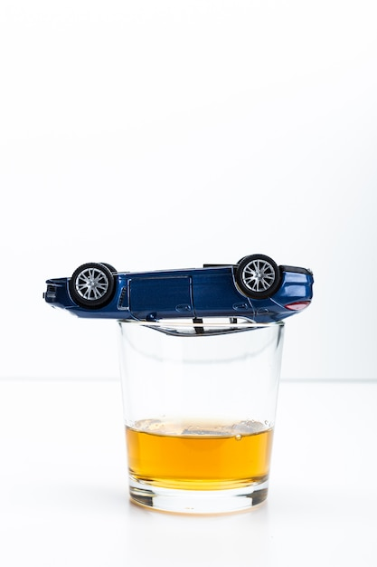 Toy car and glass of whiskey metaphor crash accident isolated on white Premium Photo