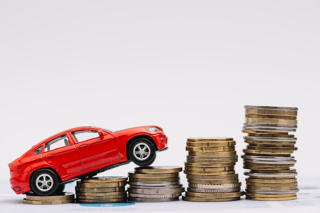 Toy car going up on the increasing stack of coins against white background Free Photo