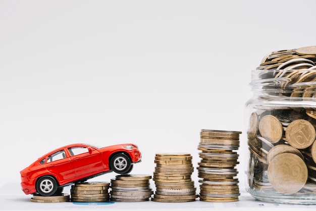 Toy car going up on the increasing stack of coins near the coins jar against white background Free Photo