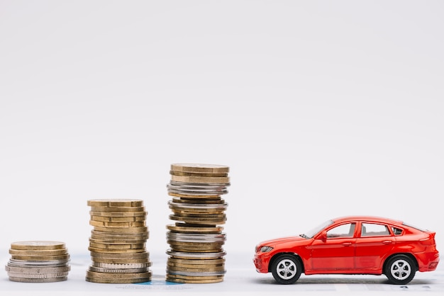 Toy car near the increasing stack of coins against white background Free Photo