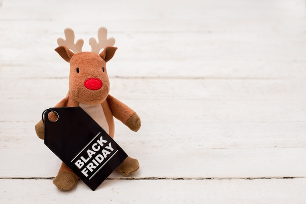 Toy deer with black friday tag on white wood  with copyspace Premium Photo