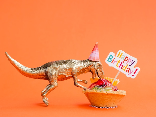 Toy dinosaur eating birthday sweets Free Photo