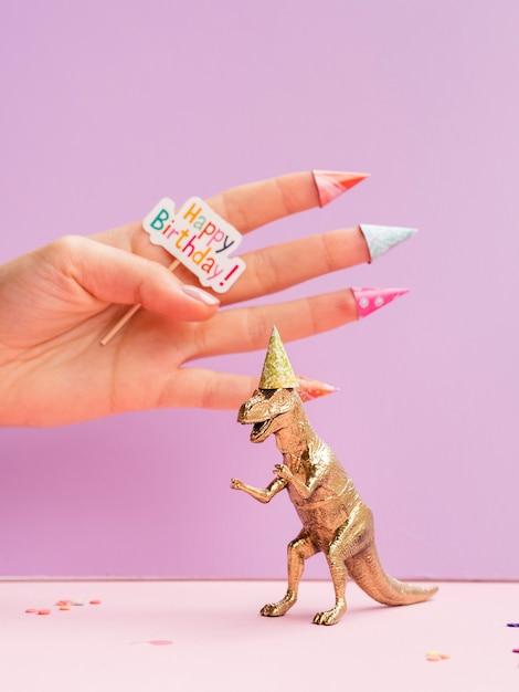 Toy dinosaur and hand holding happy birthday sign Free Photo