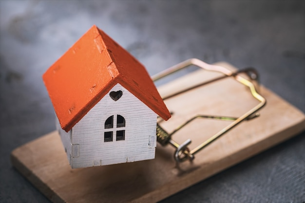 Premium Photo A Toy House In A Mousetrap Concept On The Topic Of Housing Traps