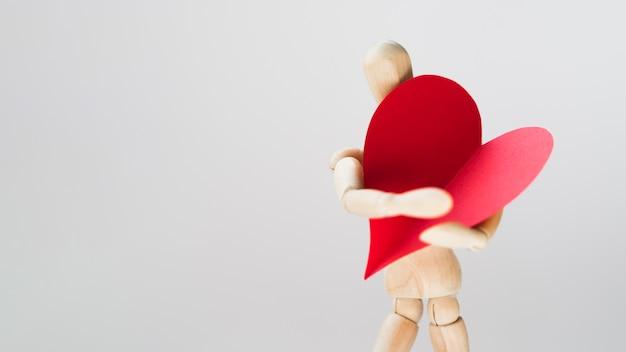 Игрушечный манекен держит сердце с копией пространства Premium Фотографии