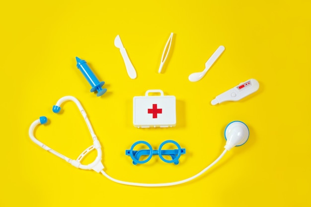 Toy medical devices on a yellow. kids medical instruments Premium Photo