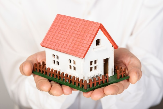 Toy model house held in hands close-up Free Photo