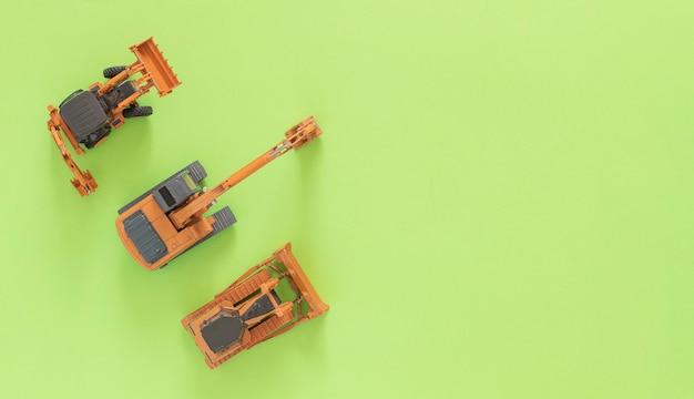 おもちゃは前部積込み機、鉱山の掘削機およびブルドーザーを模倣します。緑の背景。コピースペース。 Premium写真