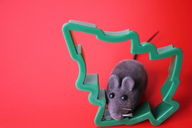 Игрушечная мышка и новогодняя елка на красном фоне Premium Фотографии