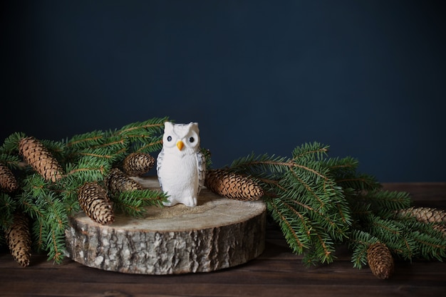 Toy owl on  tree cut with fir  branches Premium Photo