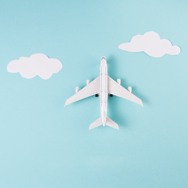 Toy plane and clouds on blue background Free Photo