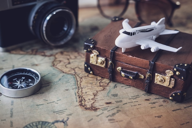Toy plane and suitcase on vintage map with copy space Premium Photo