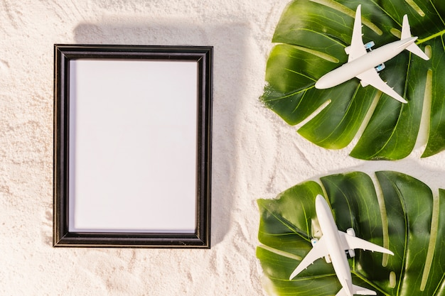 Toy planes on monstera leaves and frame Free Photo