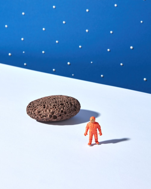 Toy plastic astronaut with stone and shadows against blue starry sky. outer space concept. Premium Photo