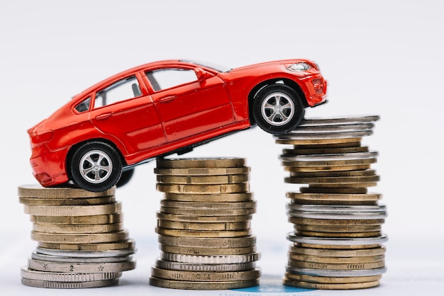 Toy red car over the stack of increasing coins against white background Free Photo
