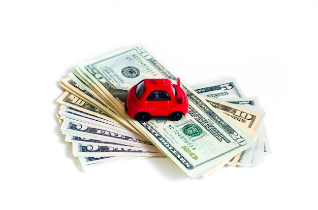 Toy red car on stack of money dollar bills. american dollars. buy car on credit. save up for vehicle. Premium Photo