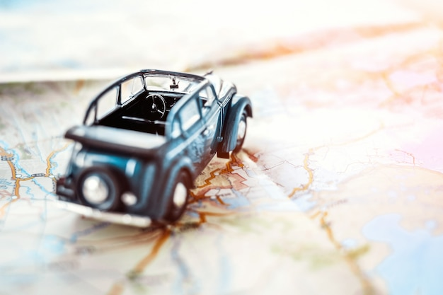 Toy retro cabrio car on the map, tourism concept Premium Photo