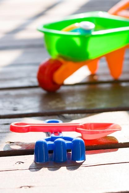Игрушечные песочные ведра и лопаты на деревянной террасе в солнечный день Premium Фотографии