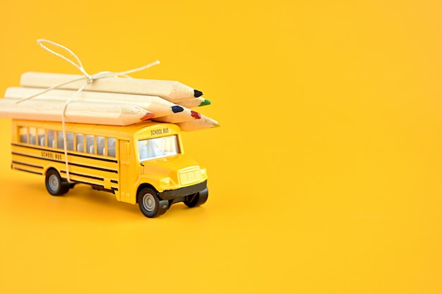 Toy school bus with pencils on the roof. Premium Photo