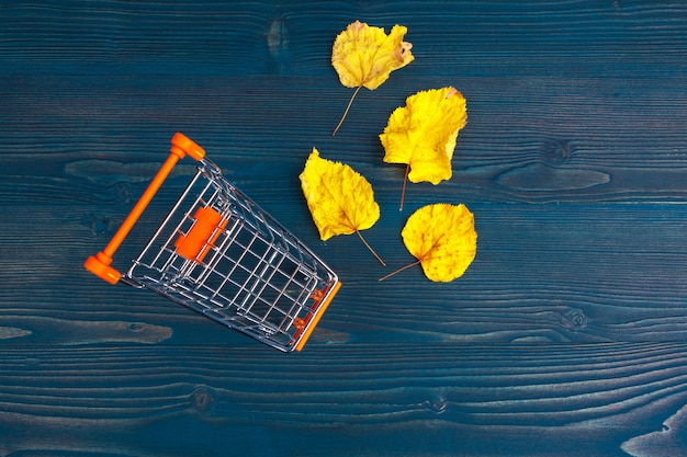 Toy shopping cart on blue wooden Premium Photo