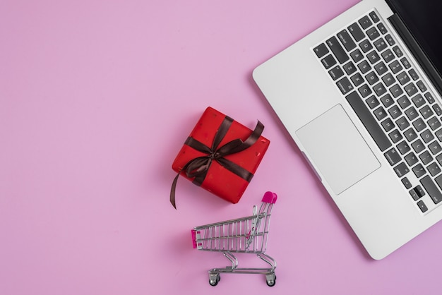 Toy shopping trolley and present near laptop keyboard Free Photo