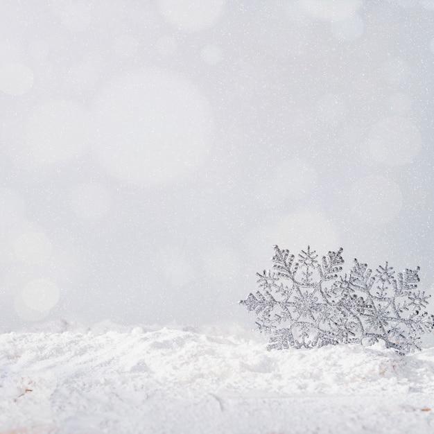 Toy snowflakes on bank of snow Free Photo