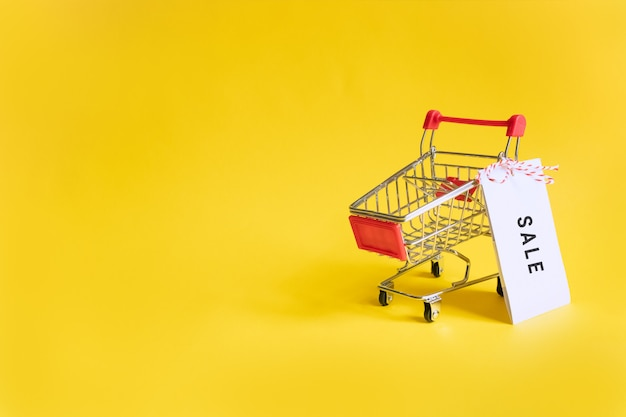 Toy supermarket cart with sale sticker on a yellow .  sales, shopping and black friday. copyspace fo