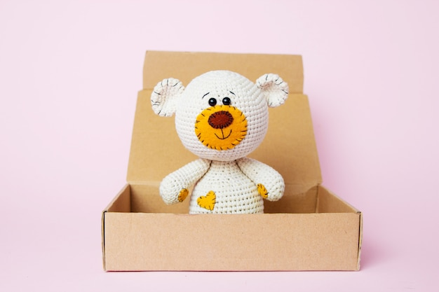 Toy teddy bear in a craft box isolated on a pink background. baby background. copy space, top view Premium Photo