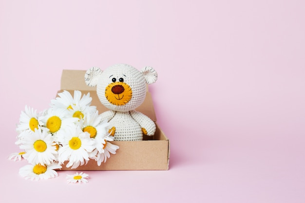 Toy teddy bear in a craft box with daisies isolated on a pink background. baby background. copy space, top view Premium Photo