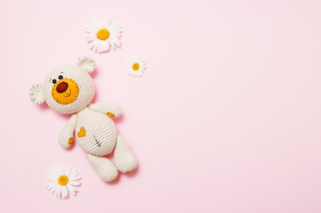 Toy teddy bear with daisies isolated on pink Premium Photo