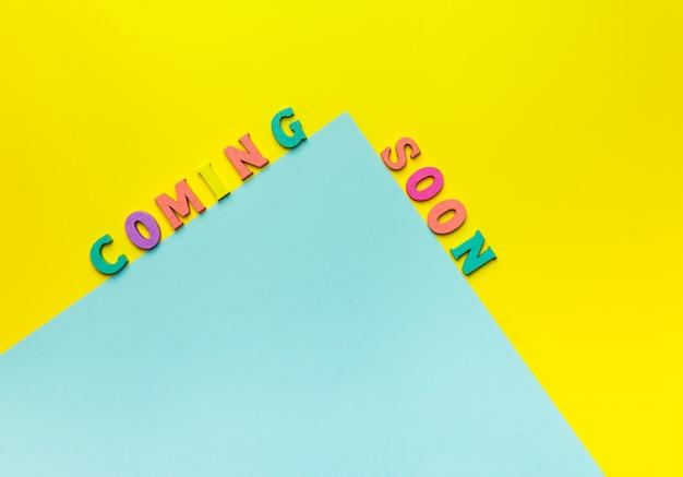 黄色の背景で近日公開予定のおもちゃの木製の手紙 Premium写真