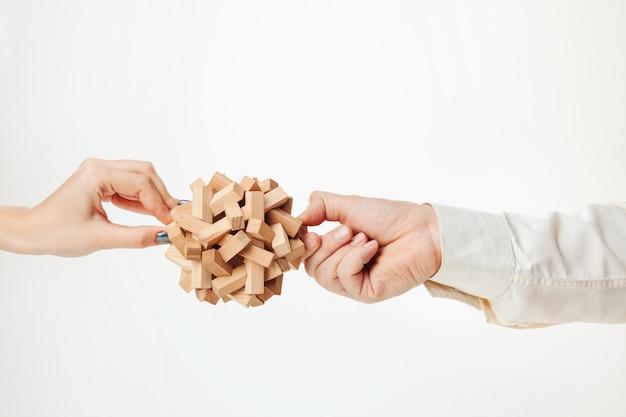 白で隔離される手でおもちゃの木製パズル 無料写真