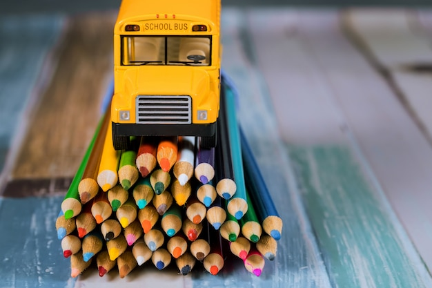 Toy yellow bus on bunch of colored pencils . Premium Photo