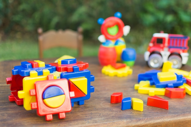 Toys made with colorful plastic blocks on wooden table Free Photo