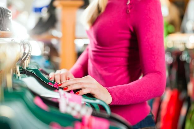 Женщина покупает tracht или dirndl в магазине Premium Фотографии