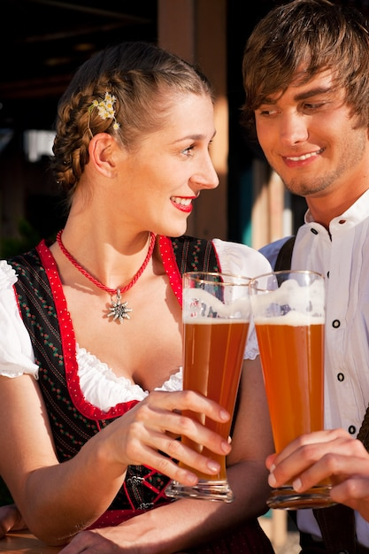 小麦ビールを飲むバイエルンtrachtのカップル Premium写真