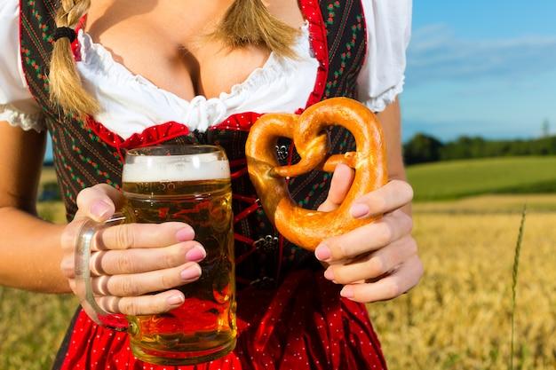 Tracht、ビール、バイエルンのプレッツェルを持つ女性 Premium写真