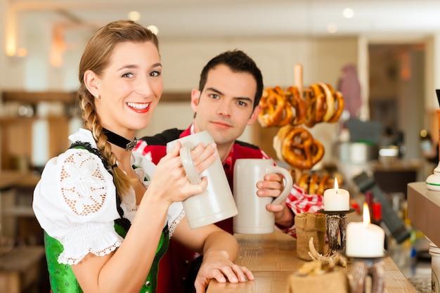 レストランやパブで伝統的なバイエルンtrachtの若いカップル Premium写真