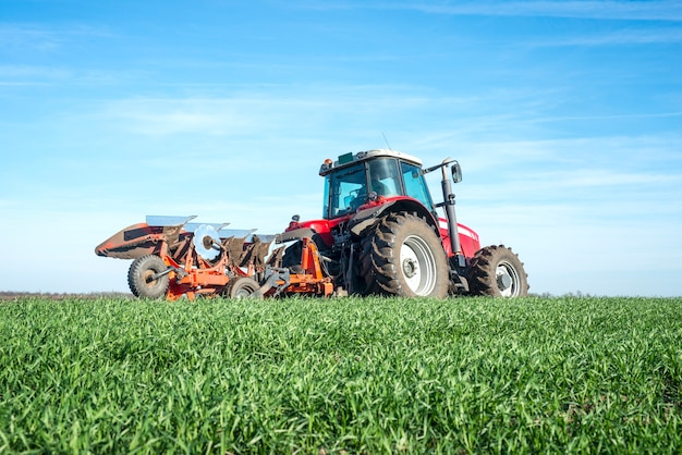 Tractor cultivating field Free Photo