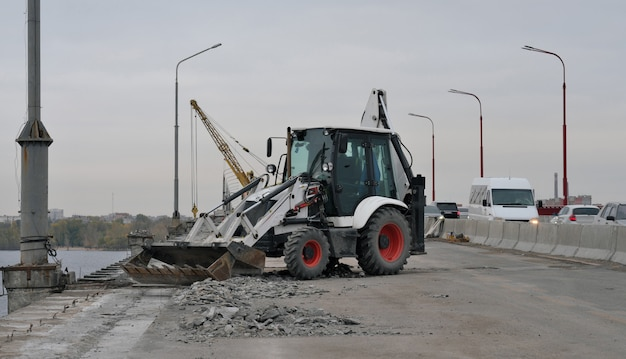 Tractor or excavator repairs bridge, removes garbage Premium Photo