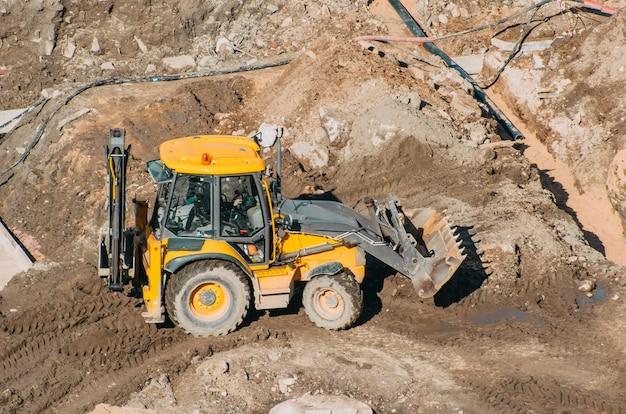 Трактор-экскаватор с ковшом проезжает по грязевым землям, вид с высоты. Premium Фотографии