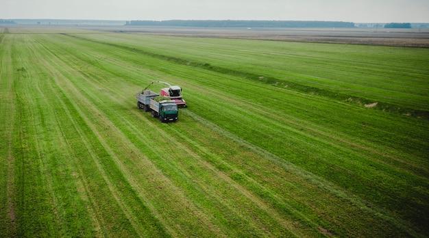 Трактор косит траву на зеленом поле с высоты птичьего полета Premium Фотографии