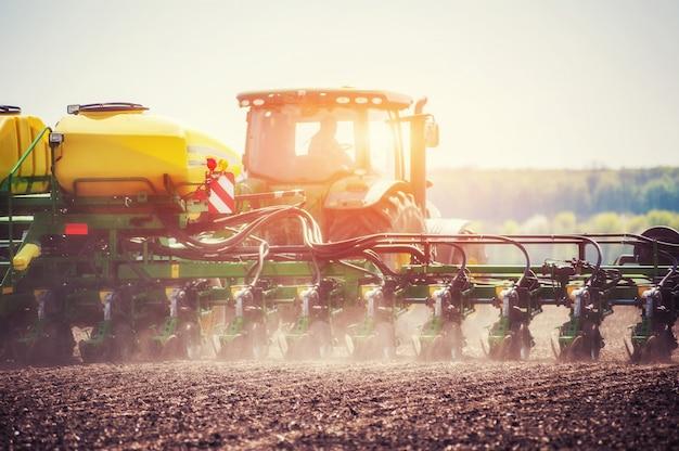 春の植栽の準備で農地を耕すトラクター Premium写真