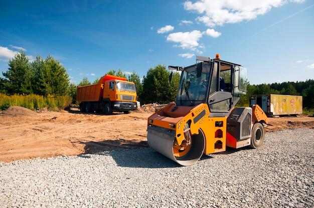 Тракторный каток уплотняет почву новой дороги Premium Фотографии