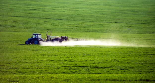 Трактор распыляет пестициды на поле с опрыскивателем летом Premium Фотографии