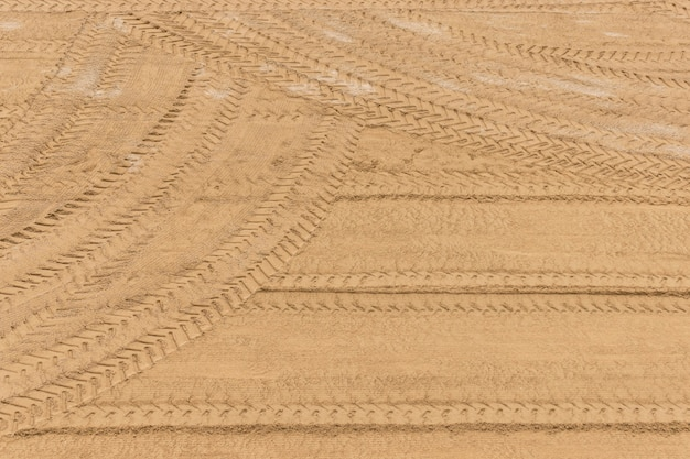 Tractor tire tracks on the sand after cleaning up. Premium Photo